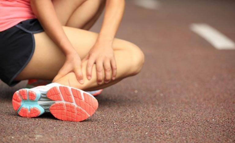 Mulher com lesão e dor no tornozelo em uma pista de corida