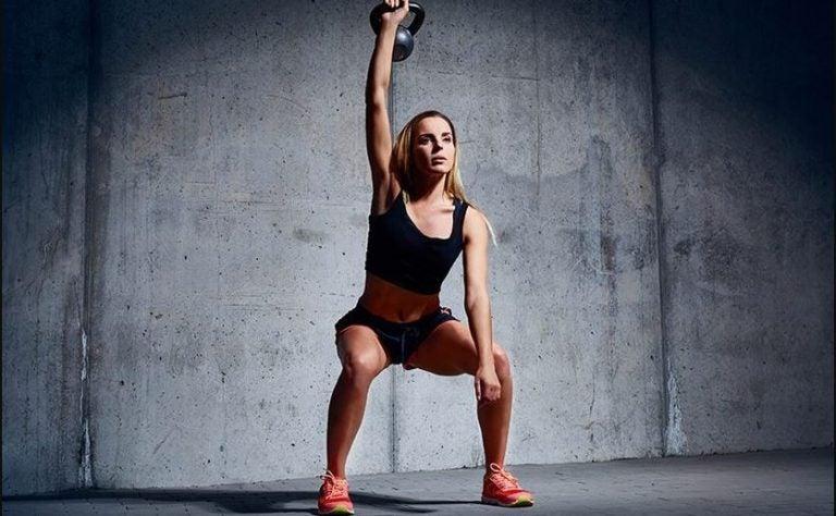 Mulher treinando as pernas com o peso ketlebell