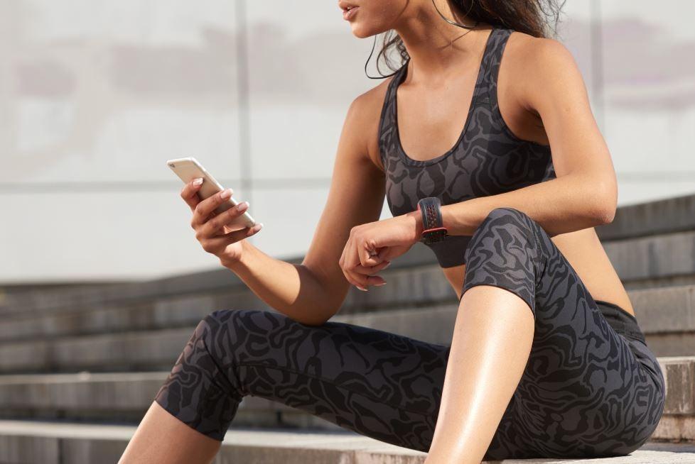 Menina com roupa de ginástica consultando celular
