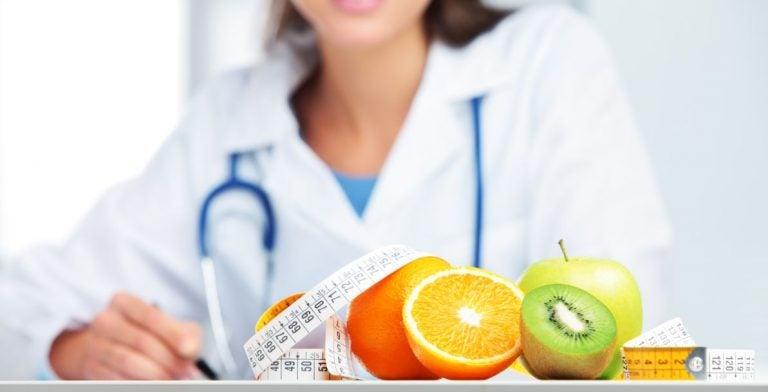Nutricionista com várias frutas e uma fita métrica