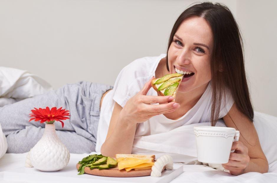 Mulher comendo torradas de queijo com abacate