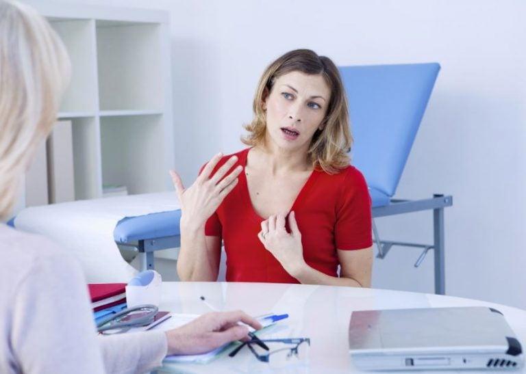Paciente explicando sintomas da menopausa para uma médica