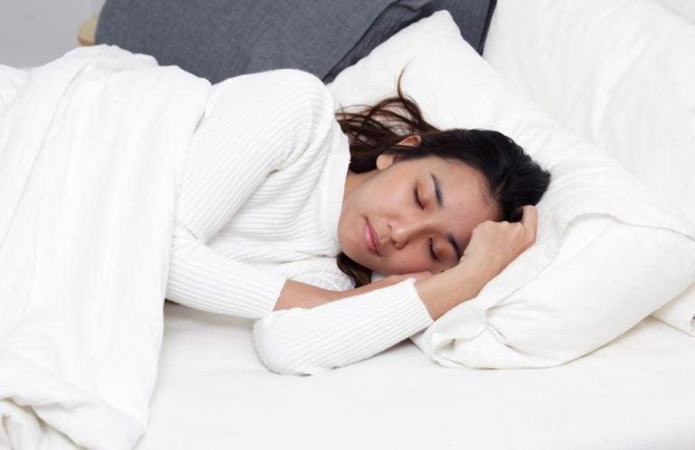 Mulher dormindo em cama branca