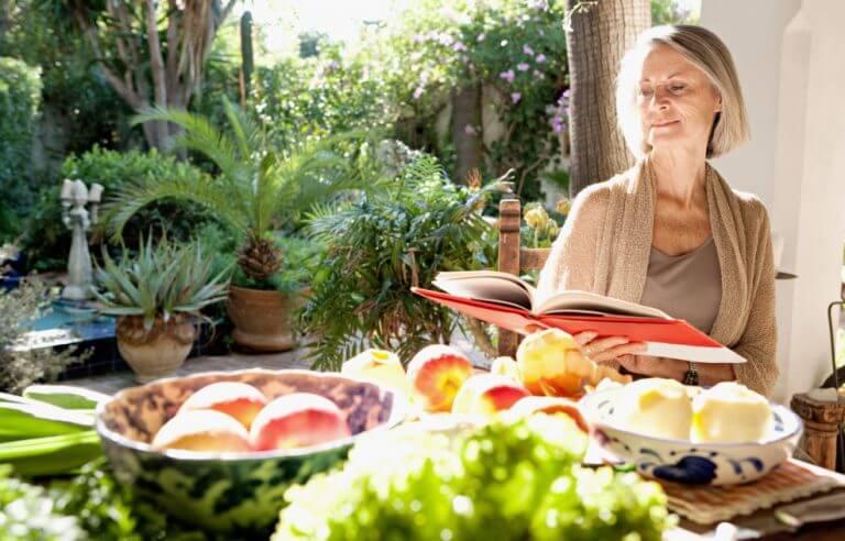 Mulher idosa lendo um livro de receitas com vários alimentos na mesa