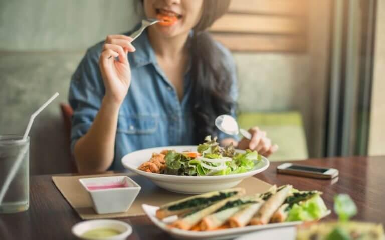 Mulher comendo um prato de salada