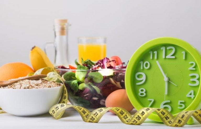 Vários alimentos saudáveis, um relógio e uma fita métrica