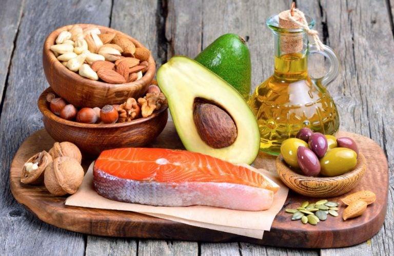 Uma tábua com vários alimentos: peixes, abacate, azeite, nozes e castanhas diversas