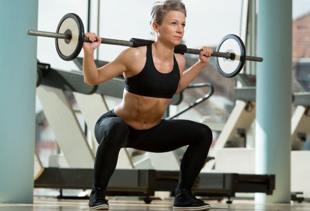 Mulher fazendo agachamento com barra de peso nas costas