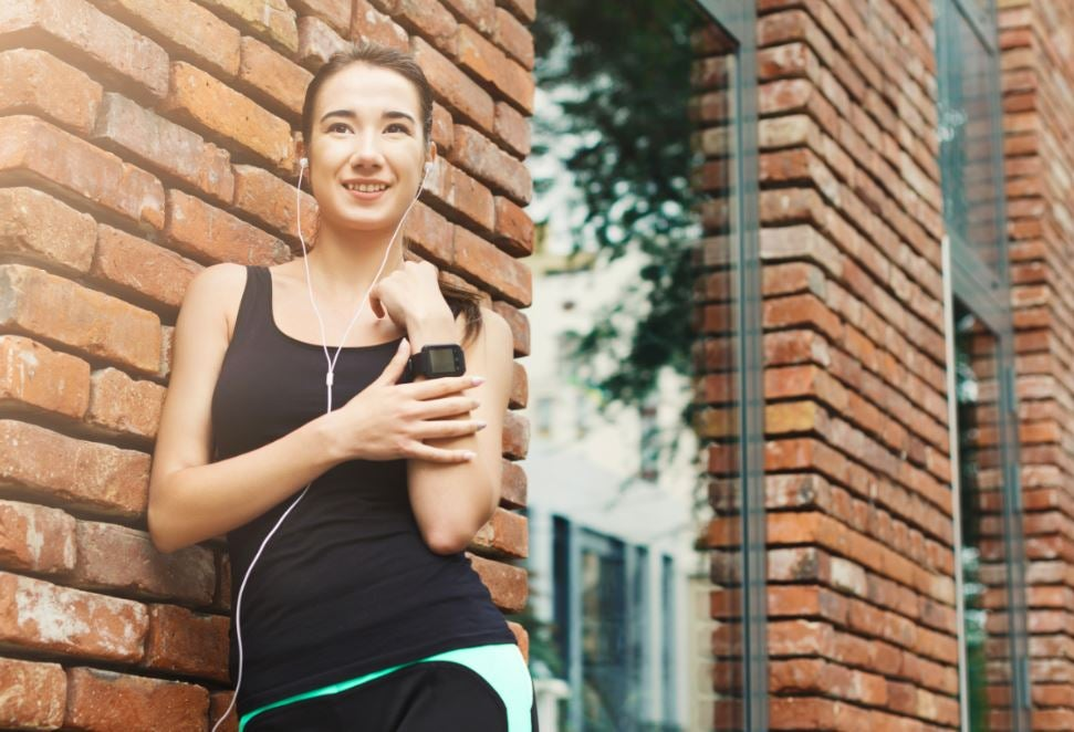 Menina encostada em uma parede com roupas de exercício.