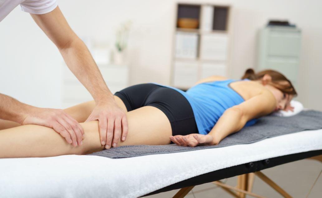Mulher recebendo massagem esportiva na cama de massagem