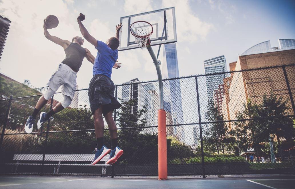 Homens jogando basquete em uma quadra ao ar livre