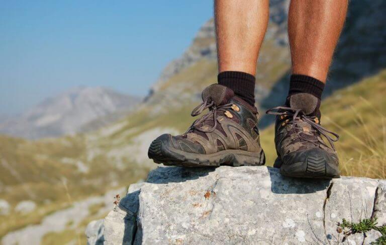 Um homem com botas para trekking em cima de uma pedra