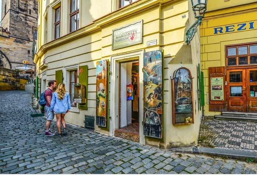 Casal de turistas observando vitrines em uma cidade antiga