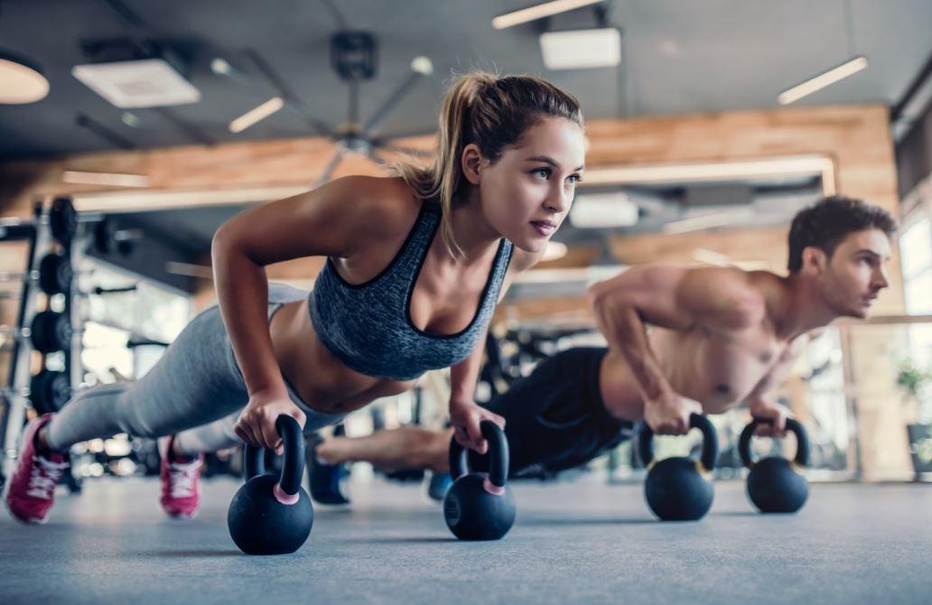 Casal fazendo exercícios com peso russo