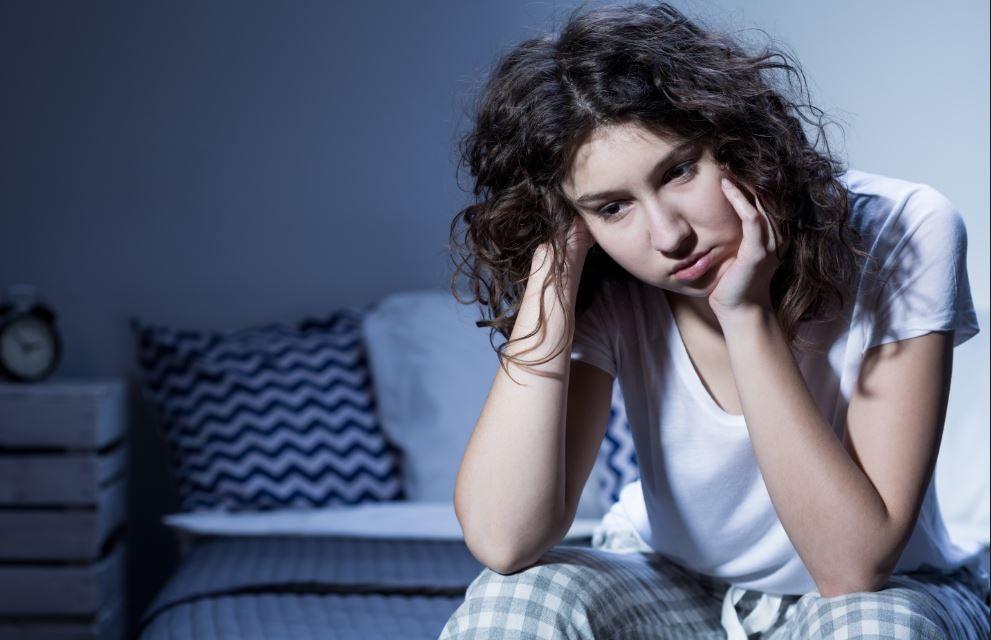 Mulher muito cansada de noite com cara de tristeza