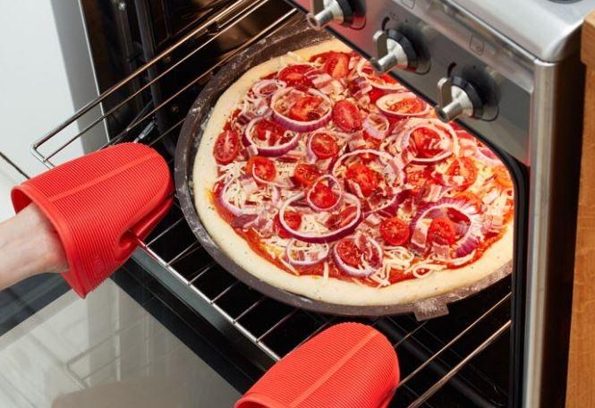 Pessoa colocando a pizza para assar
