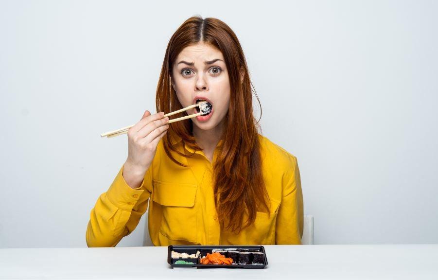 Menina comendo sushi com uma expressão de surpresa