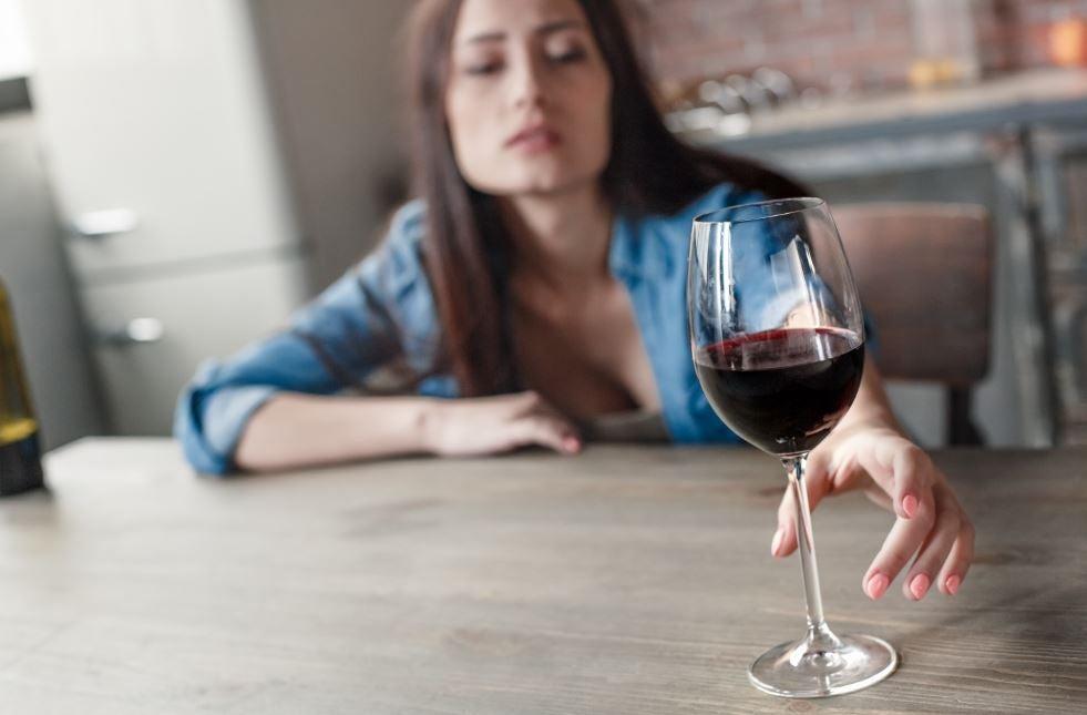 Mulher alcoolizada tomando uma taça de vinho