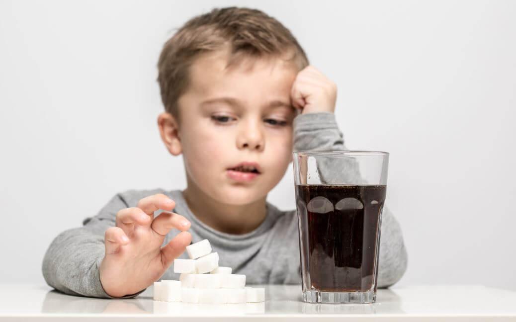 criança com bebida açucarada
