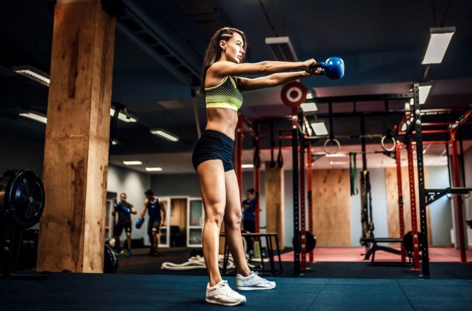 Mulher fazendo crossfit na academia com ketlebell
