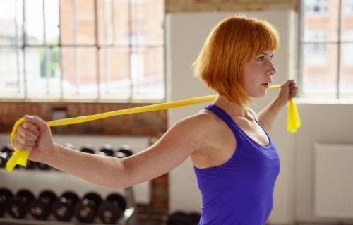 Mulher fazendo exercício com fita elástica para as costas
