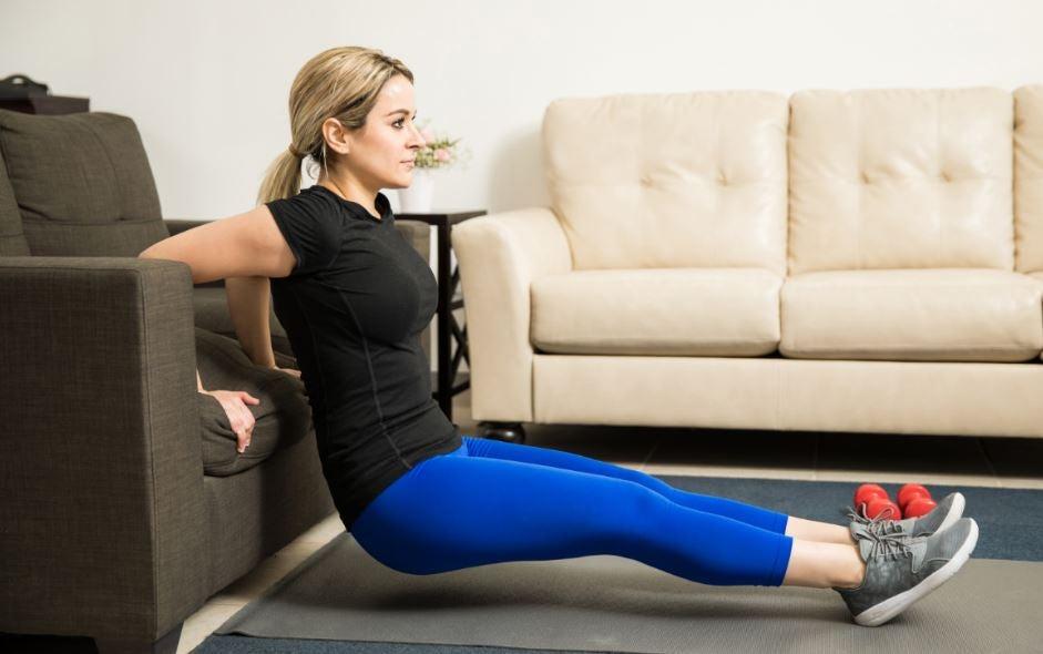 Mulher treinando em casa com um sofá