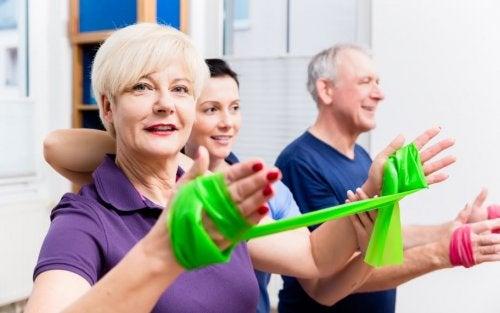 Idosos trabalhando com a fita elástica para exercitar as costas