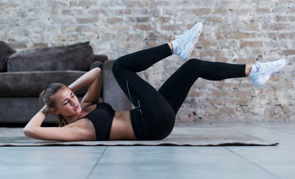 Mulher fazendo exercício abdominal chamado bicicleta