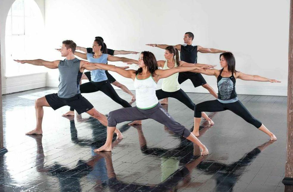 Alunos fazendo yoga em uma aula na academia