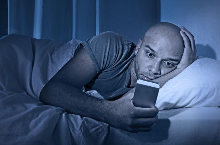Homem sem dormir com o celular