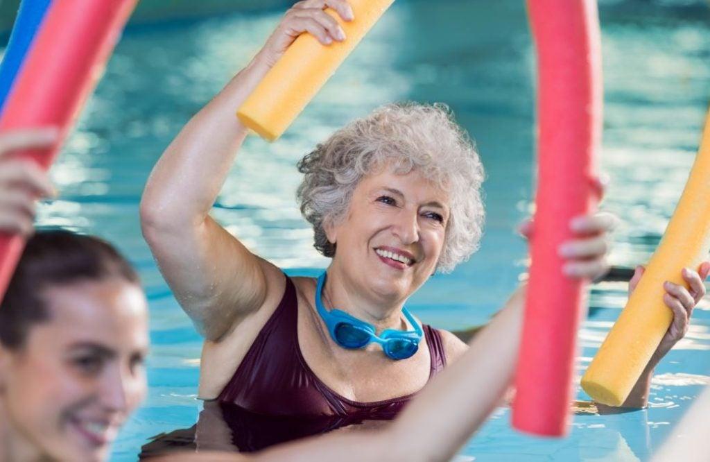Senhora fazendo exercícios de hidroginástica com boia espaguete
