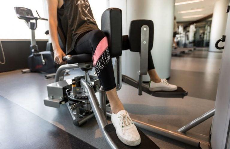 Mulher fazendo cadeira adutora na academia