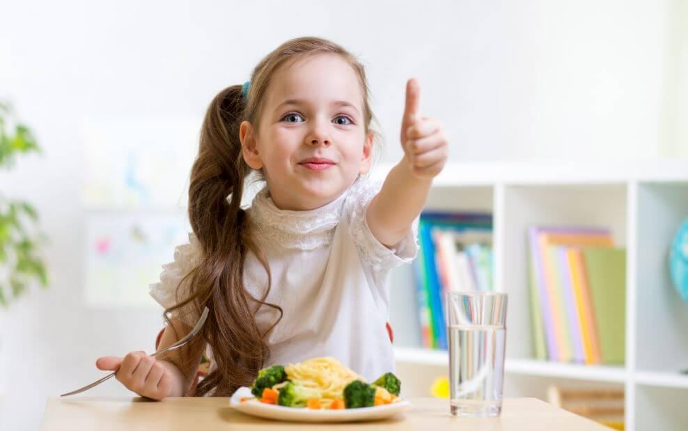 Garotinha dando ok para a câmera comendo um prato de vegetais