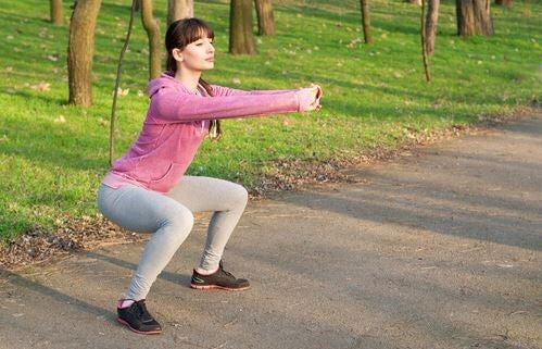 Uma mulher fazendo agachamento em um parque