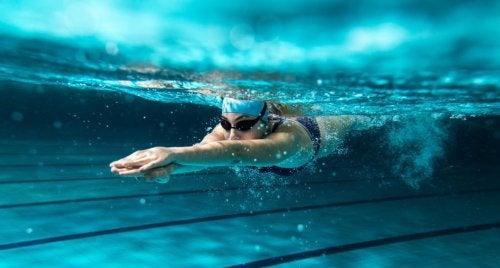 Mulher nadando com touca e óculos de natação