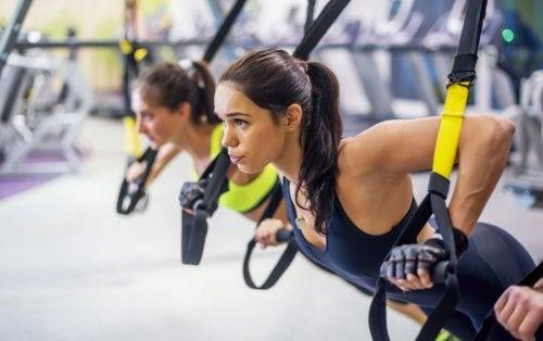 mulher realizando exercício para peitoral no TRX