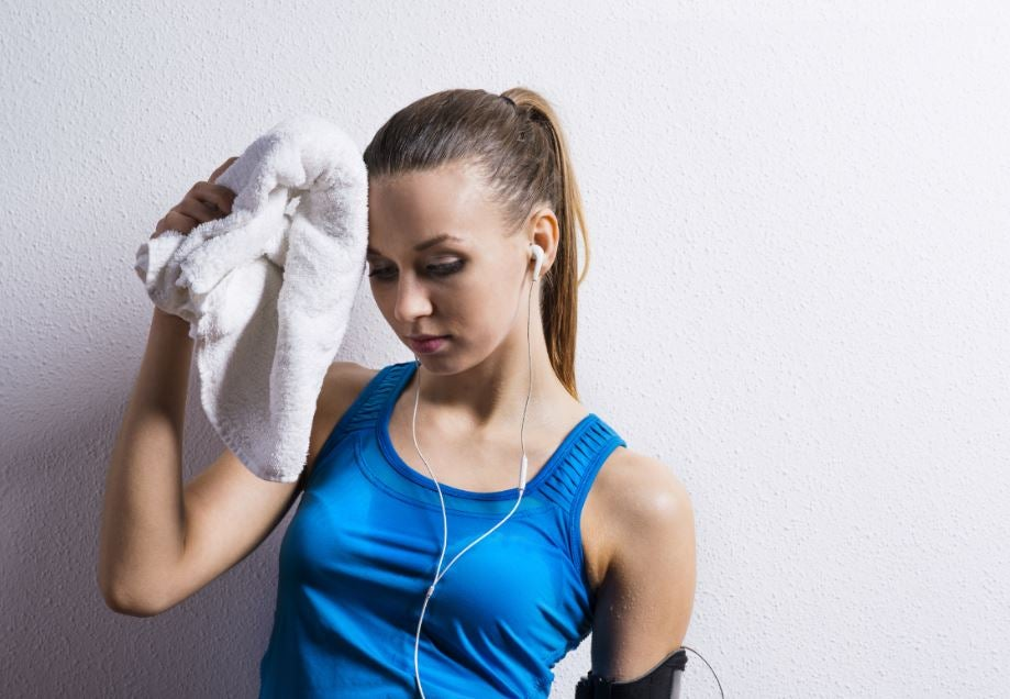 Mulher secando seu suor na academia com uma toalha