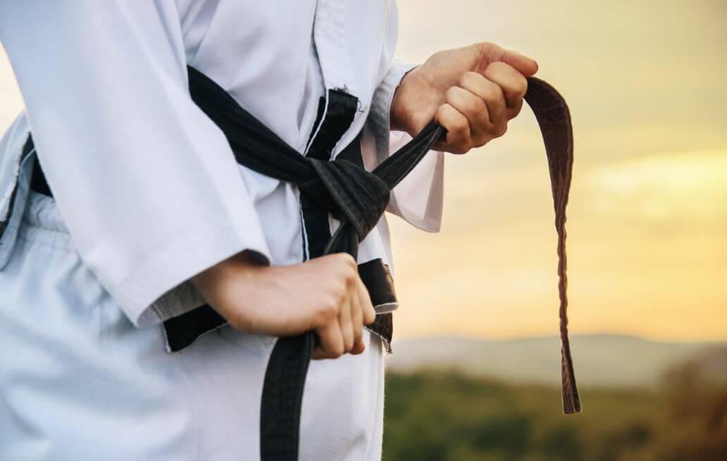 Pessoa com roupa de judô amarrando a faixa preta