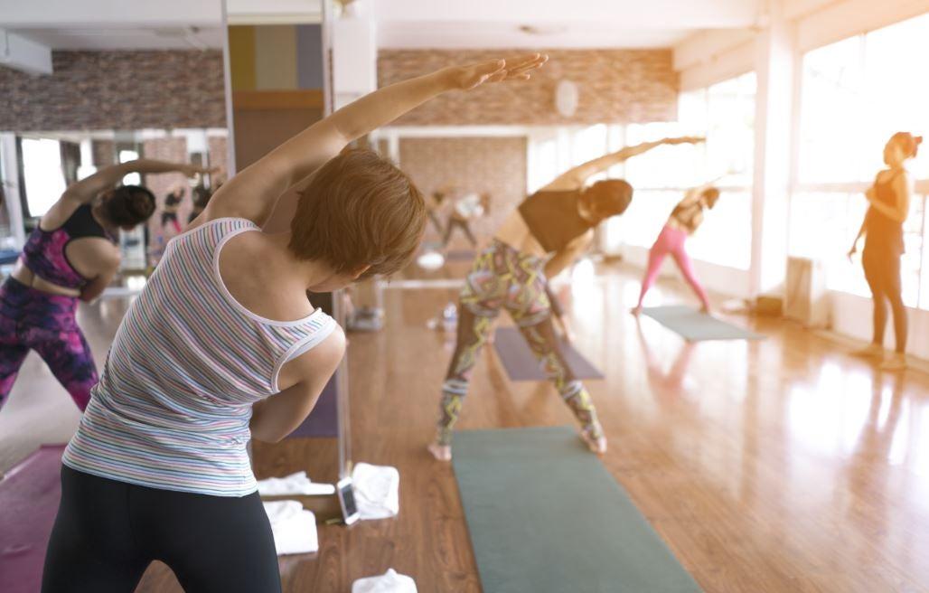 Alunas fazendo exercícios de flexibilidade na academia