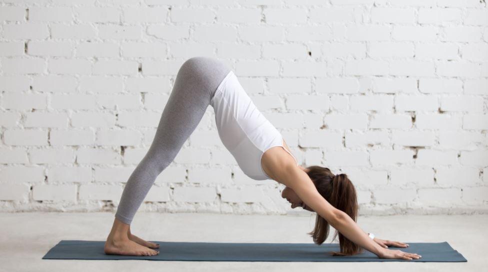 Mulher realizando a postura de Yoga do cachorro olhando para baixo