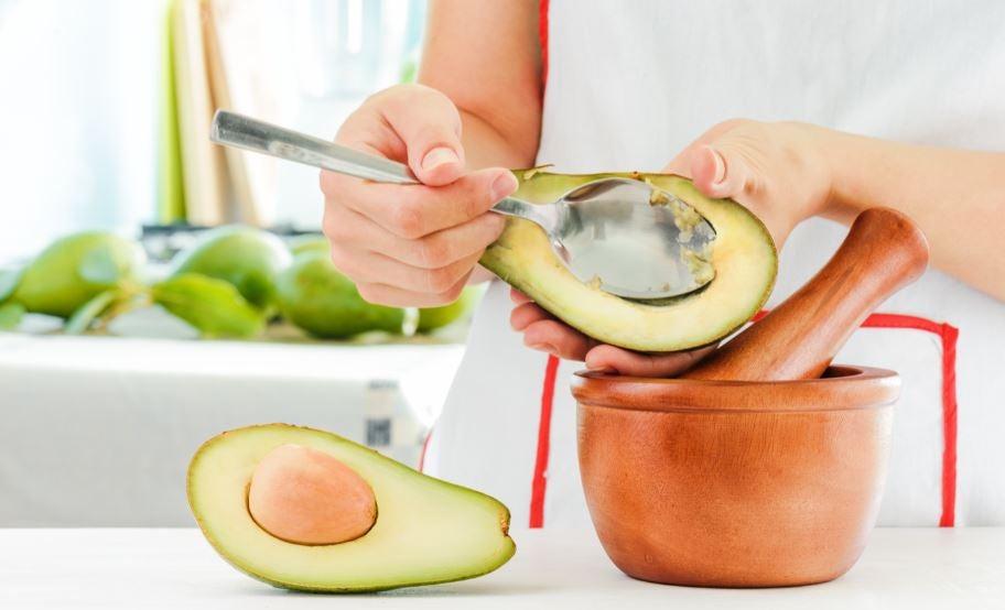 Mulher abrindo um abacate