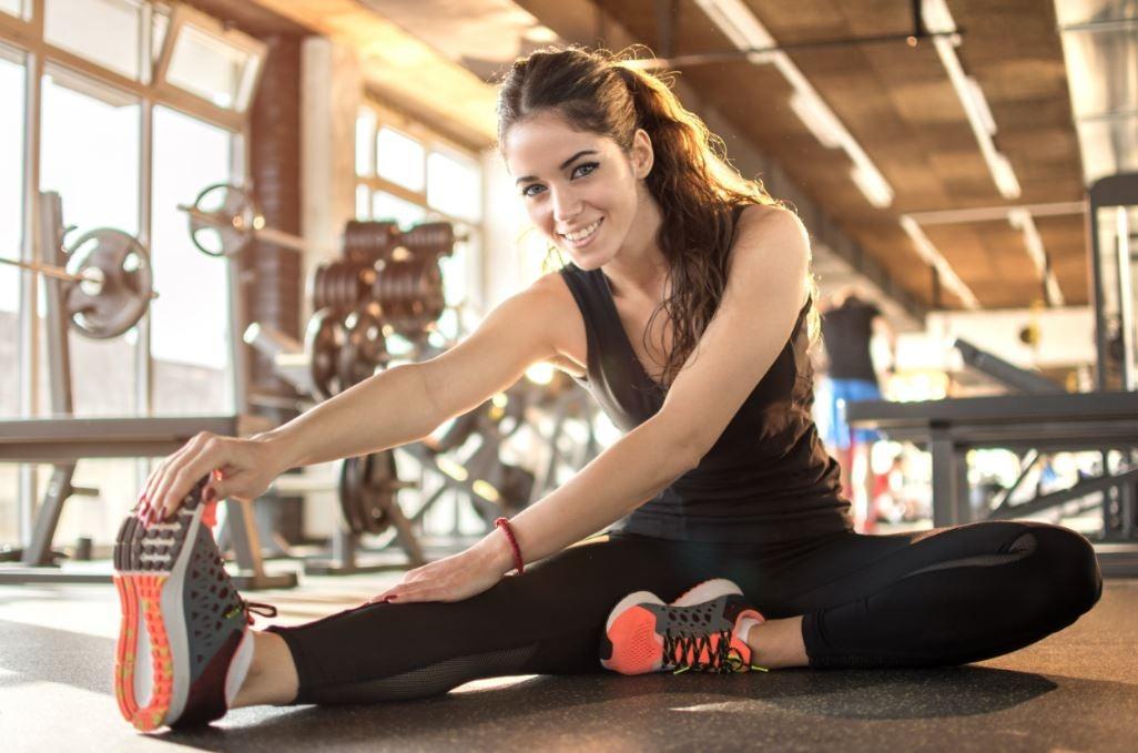 Mulher alongando as pernas em uma academia