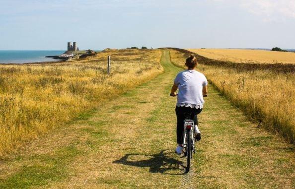 Menina pedalando no campo