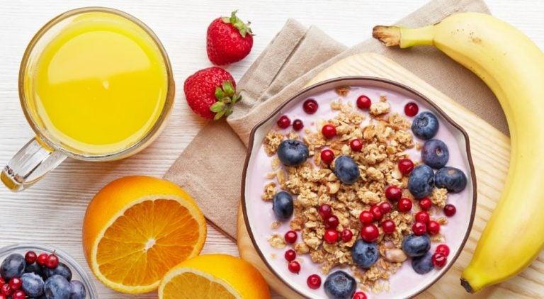 Tigela de iogurte com cereais e frutas vermelhas, suco natural de laranja e banana