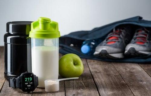Shake de proteína do lado de uma mochila com um tênis de academia