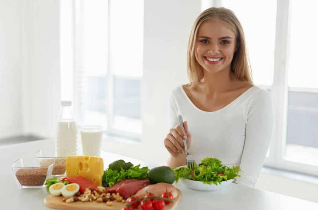 Mulher com ´vários alimentos saudável como legumes e frutas