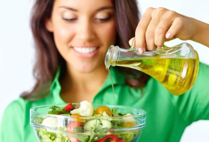 Mulher colocando azeite na salada