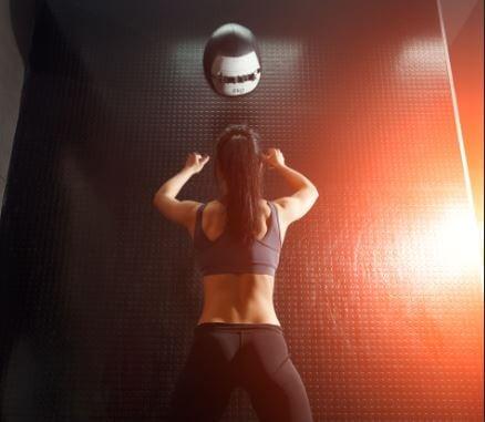 Mulher fazendo exercício com bola medicinal na parede