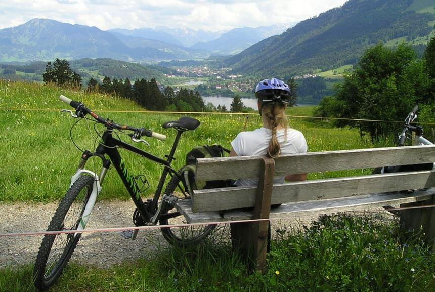 Mulher descansando com uma bicicleta nas montanhas