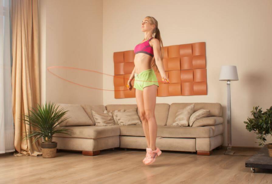 Mulher pulando corda em casa